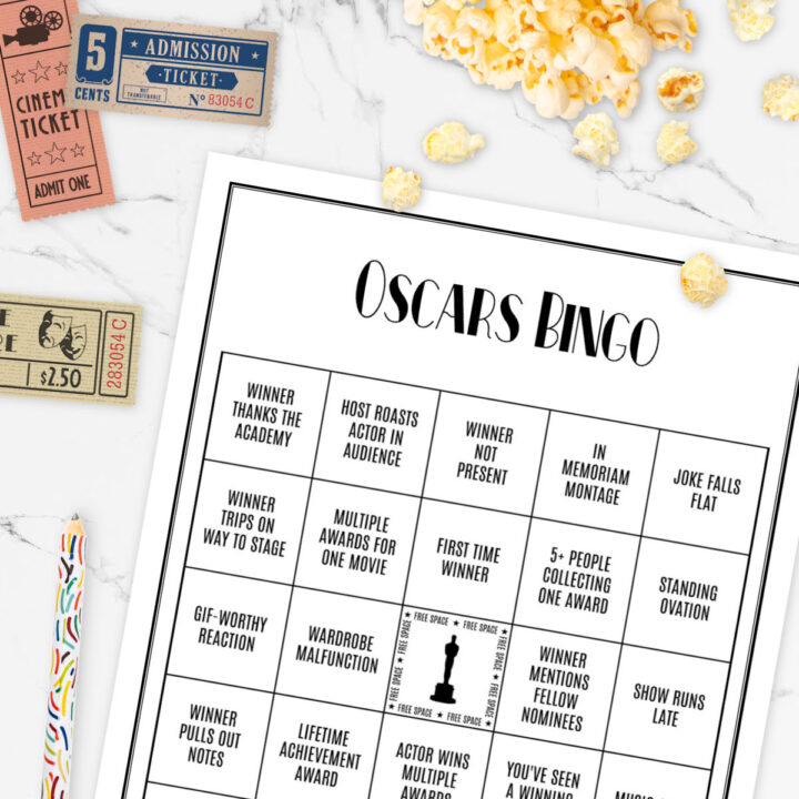 Oscars Bingo game, vintage movie tickets, and popcorn kernels on a marble table.