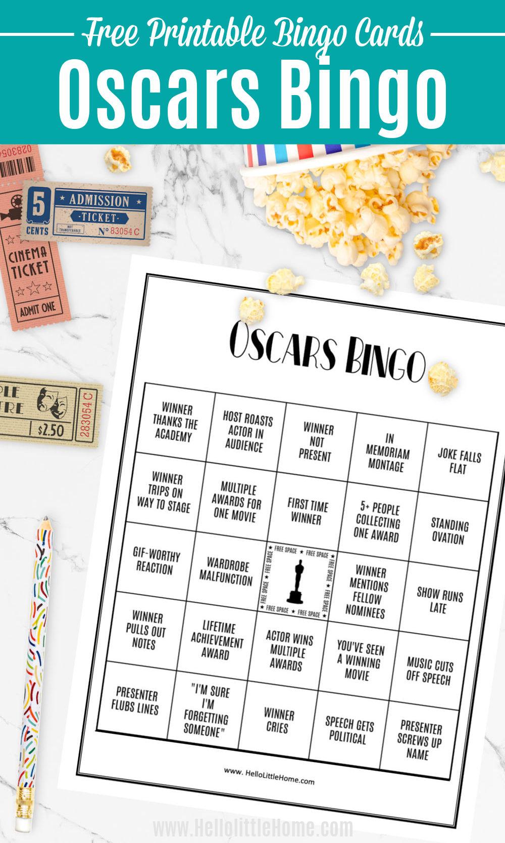 An Oscars Bingo Card, popcorn, movie tickets, and a pencil on a marble table.