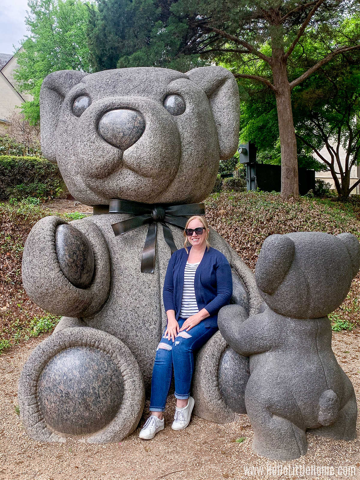 A woman sitting in the lap of a giant teddy statue in the park.