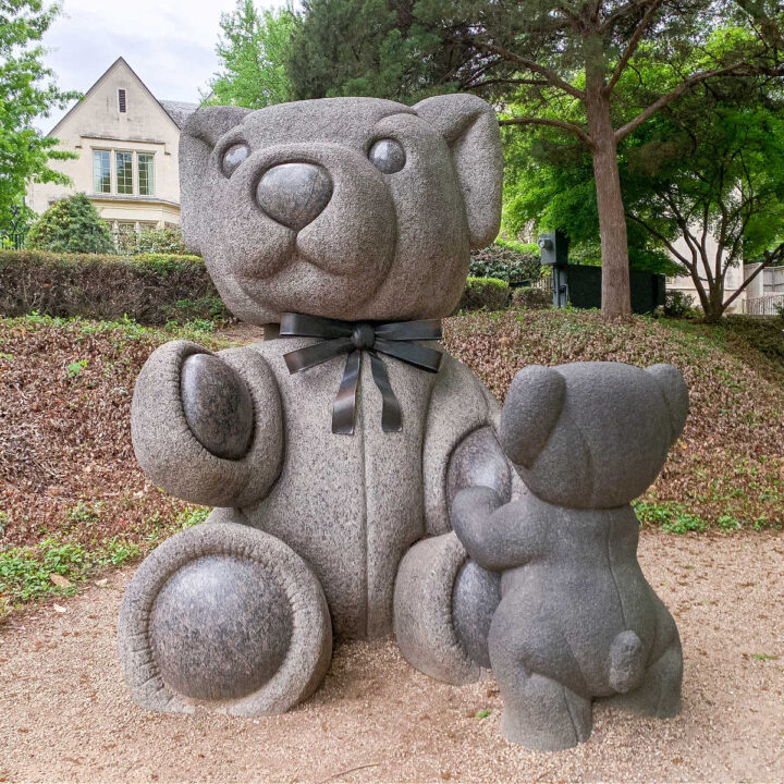Two bear statues with trees and a house in the background in Teddy Bear Park in Dallas.