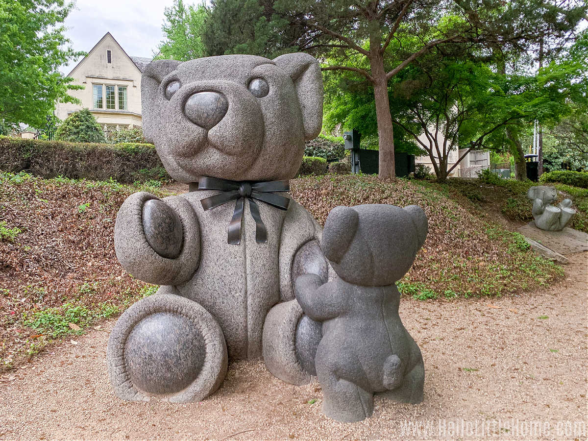 A giant teddy statue and a smaller one facing it with trees and a house in the background.