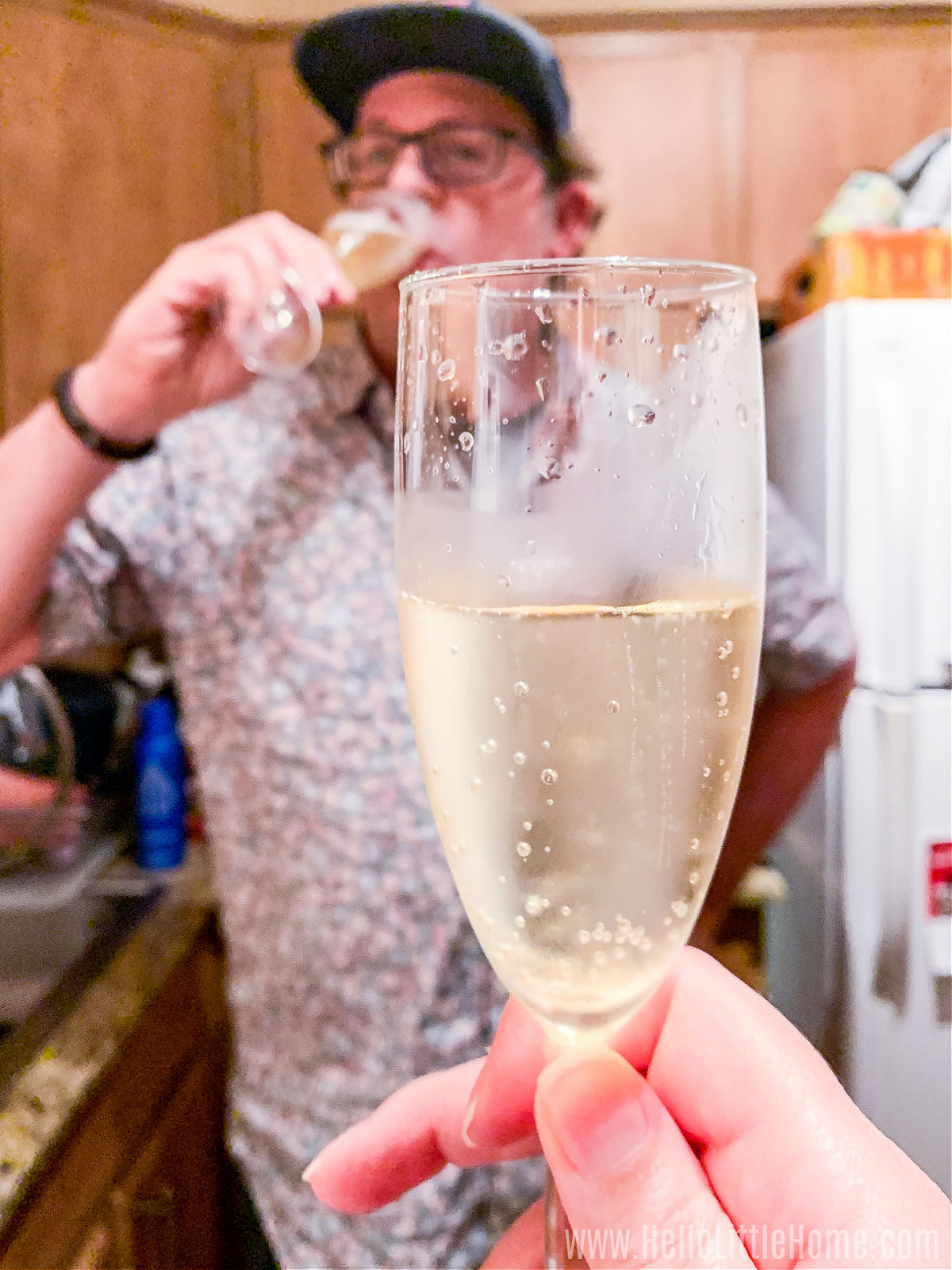 A hand holding a champagne flute in front of a man drinking champagne.