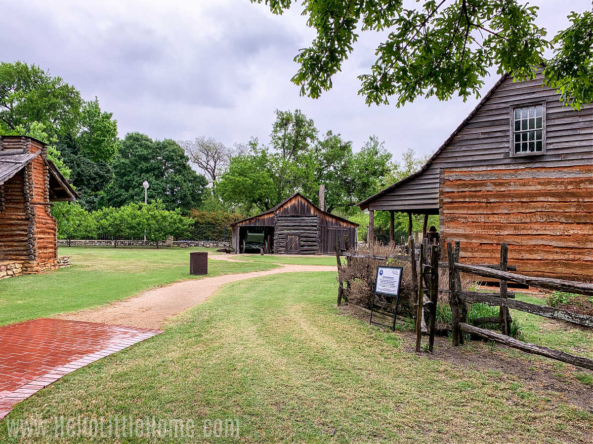 Three wooden buildings around a grassy area in the Farmers Branch Historical Park.