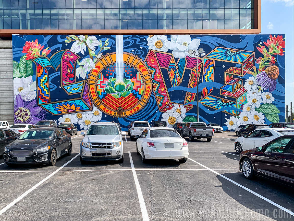 Cars parked in front of a large mural on a building.