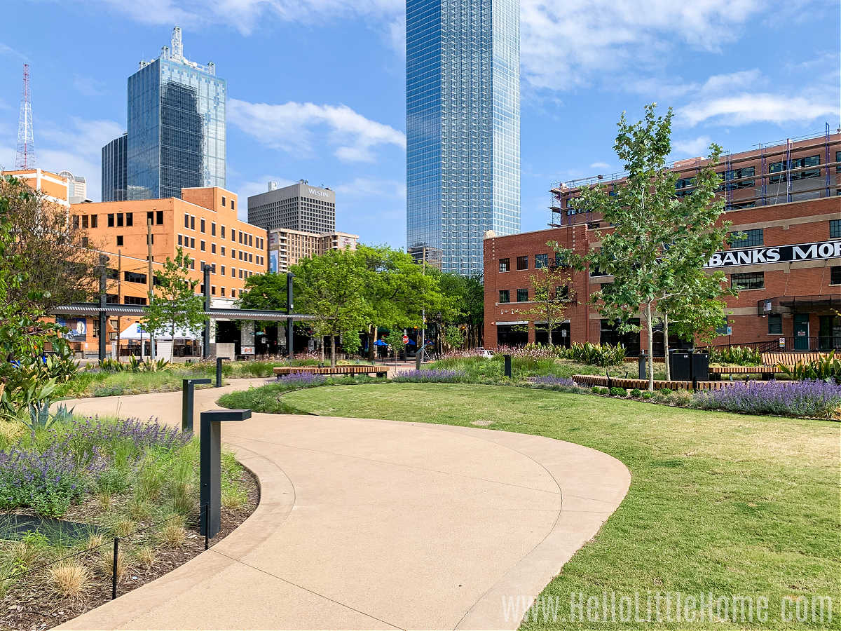 A path leading through West End Square in Dallas with tall buildings in the background.