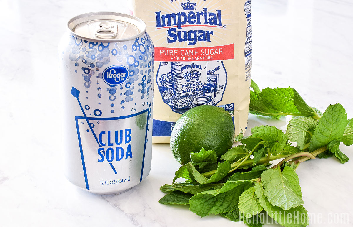 Recipe ingredients (club soda, mint, sugar, and limes) arranged on a marble counter.