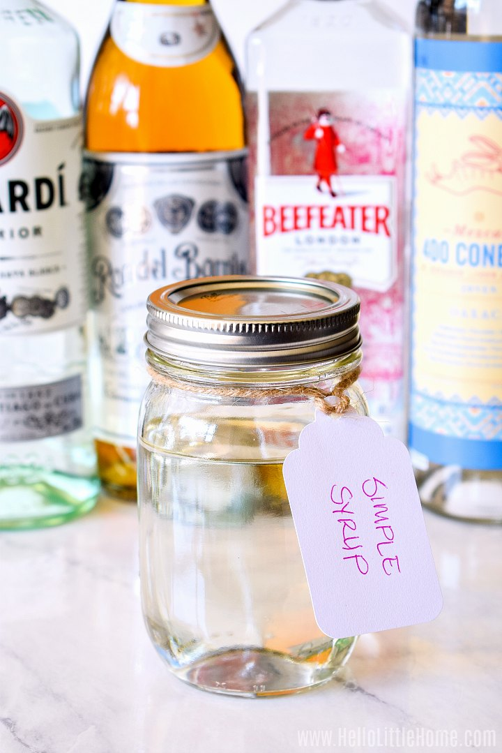 A jar of syrup with a white label tied around its neck with liquor bottles in the background.