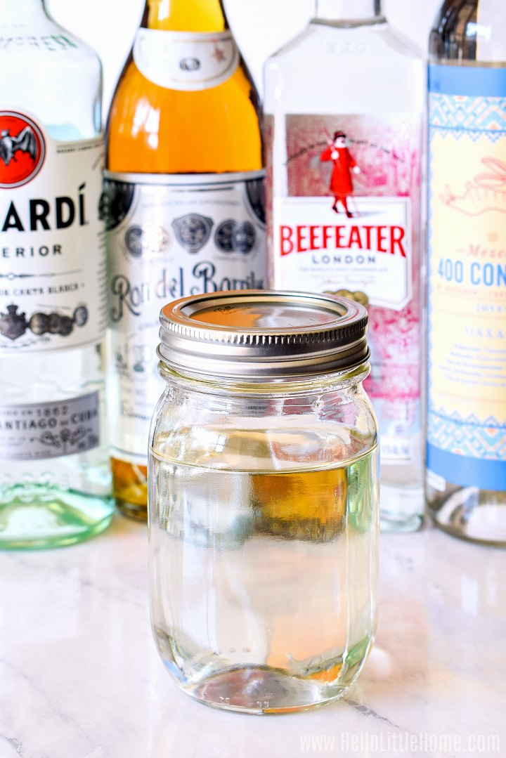 A jar of the finished recipe surrounded by liquor bottles.