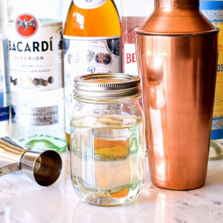 A jar of simple syrup surrounded by a jigger, cocktail shaker, and liquor bottles.