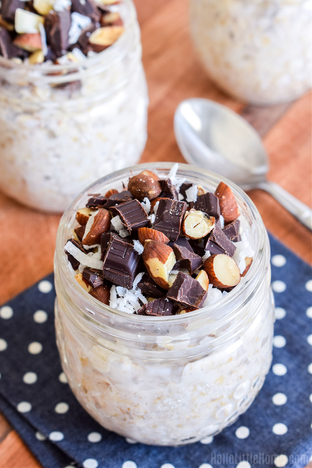 Jars of Chocolate Coconut Overnight Oats, a napkin, and spoon on a wood board.