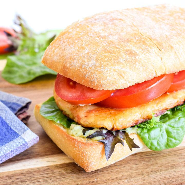 Closeup of a Halloumi Sandwich on a wood cutting board.