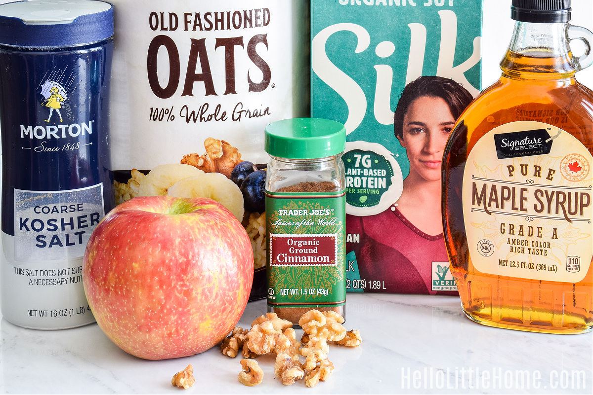 Recipe ingredients for apple oatmeal arranged on a marble counter.